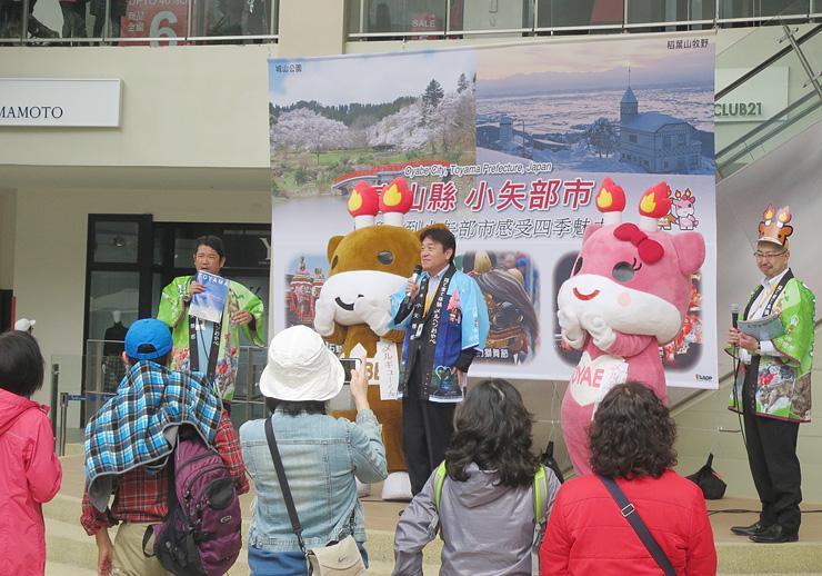 ステージで小矢部市をPRする桜井市長とメルギューくんたち
