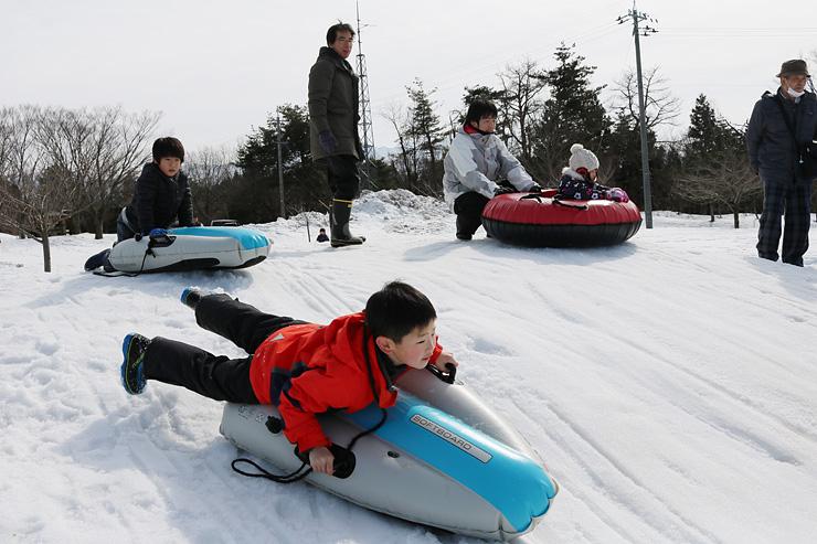 スノーチューブやそりに乗って楽しむ子どもたち=くろべ牧場まきばの風