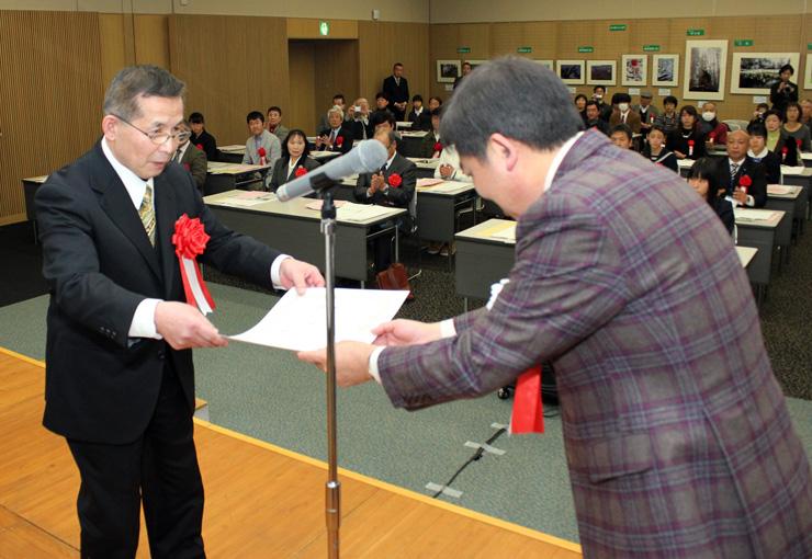 一般の部大賞に輝き、森市長から表彰状を受け取る水家さん(左)=富山国際会議場