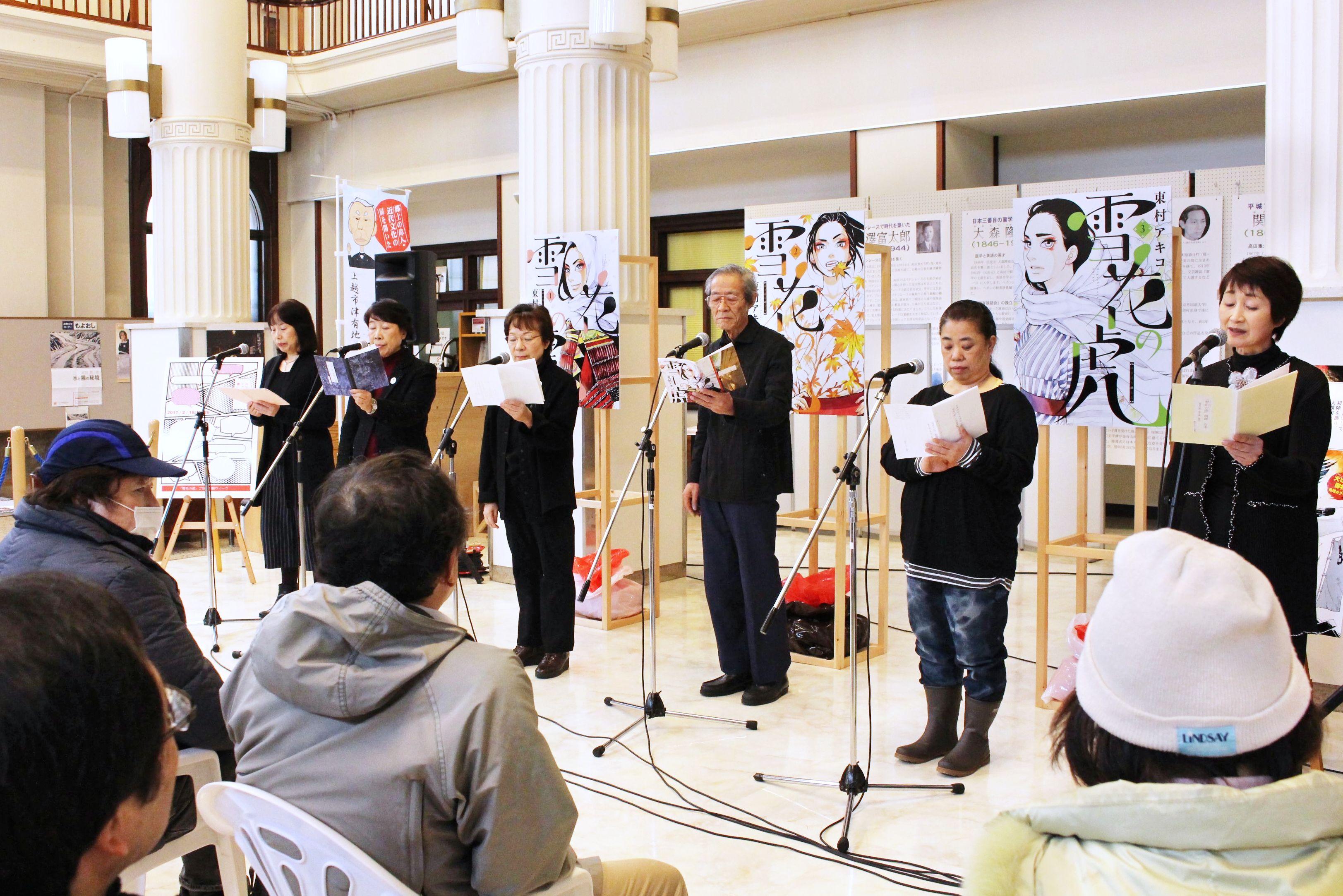 漫画「雪花の虎」の一場面を朗読する市民グループ=18日、上越市本町3