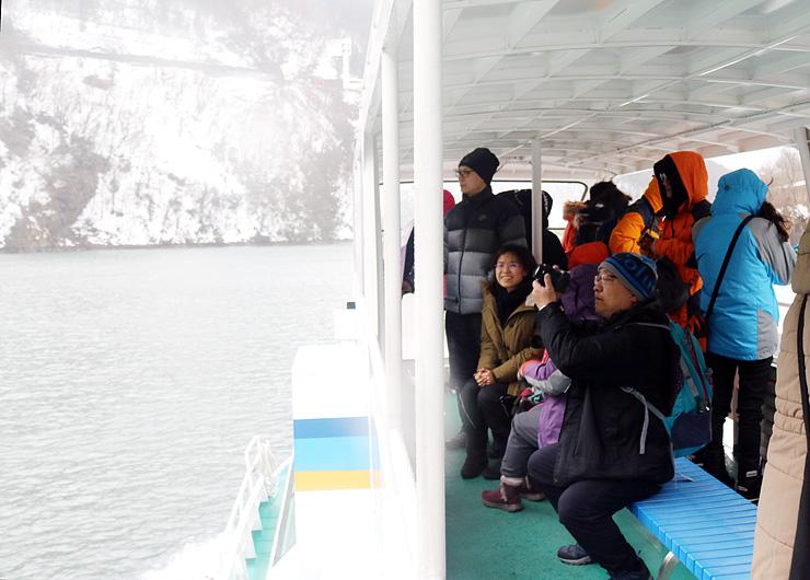 遊覧船に乗り、雪景色を楽しむ香港からの観光客
