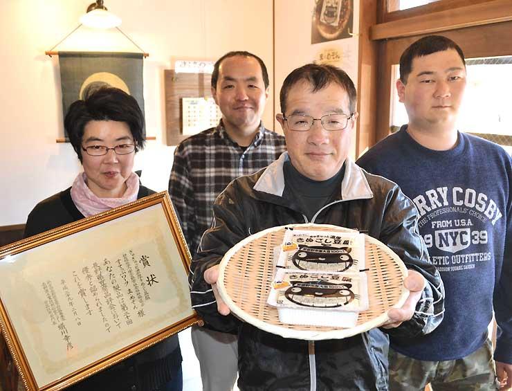 審査長賞を受けた絹ごし豆腐を手に喜ぶ利用者ら