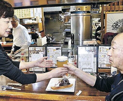 ベルギービールを提供する店員(左)=珠洲市飯田町