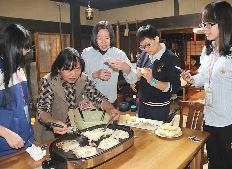 台湾の生徒たちと一緒にお好み焼きを作る是石さん(左から2人目)=16日、伊那市平沢