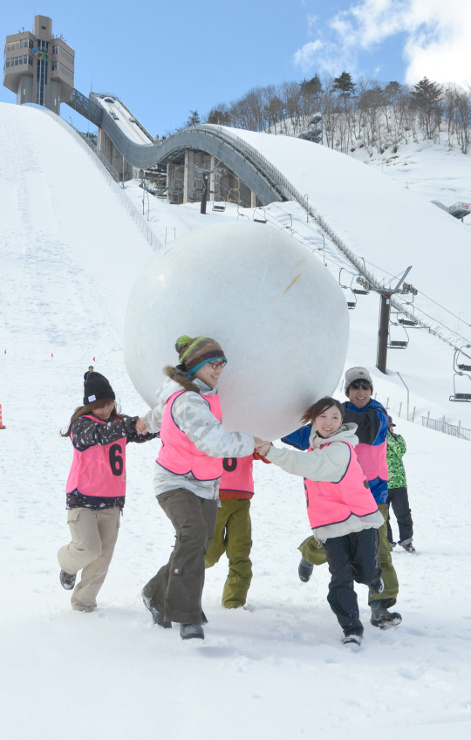 「おとなの雪上運動会」で大玉リレーをする参加者=25日、白馬村の白馬ジャンプ競技場