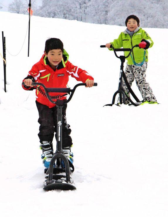 さまざまなアイテムで雪遊びを楽しむ子どもたち=十日町市松之山天水島
