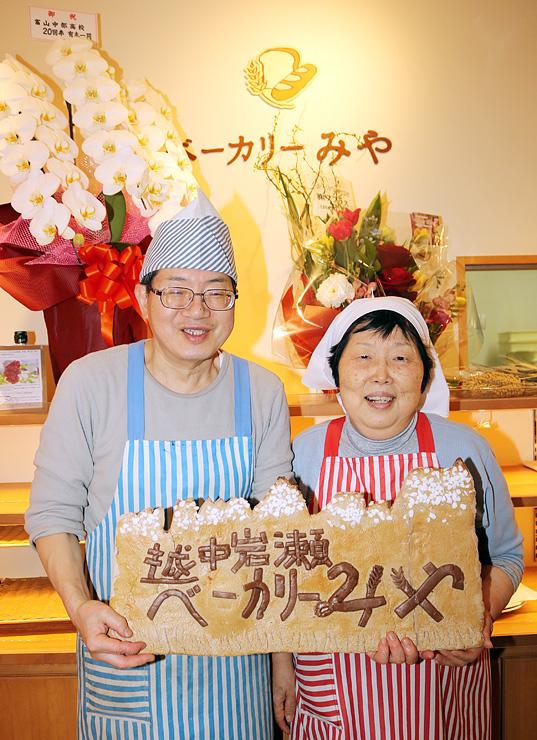 立山連峰をかたどったパンを持ち笑顔を見せる宮腰さん(左)と妻の恵美子さん=越中岩瀬ベーカリーみや