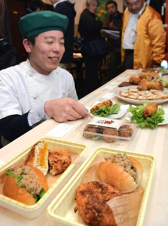 カボチャを挟んだメンチカツや、炒めた野沢菜とそぼろを挟んだロールパン(手前)などが並んだスワカツの発表会=28日、下諏訪町