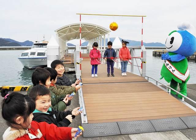 テープカットなどを行い、観光船の今季運航開始を祝う園児たち=1日、福井県おおい町成海の「うみんぴあ大飯」