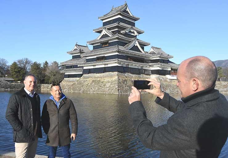 国宝松本城を背に記念撮影する外国人観光客。同城を訪れる外国人の数も、昨年度を既に上回っている=3日、松本市