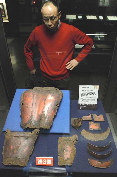 展示中の甲冑(かっちゅう)を見る降幡学芸員。一番大きな左上は、背中を覆うための物と考えられている=3日、長野市の真田宝物館