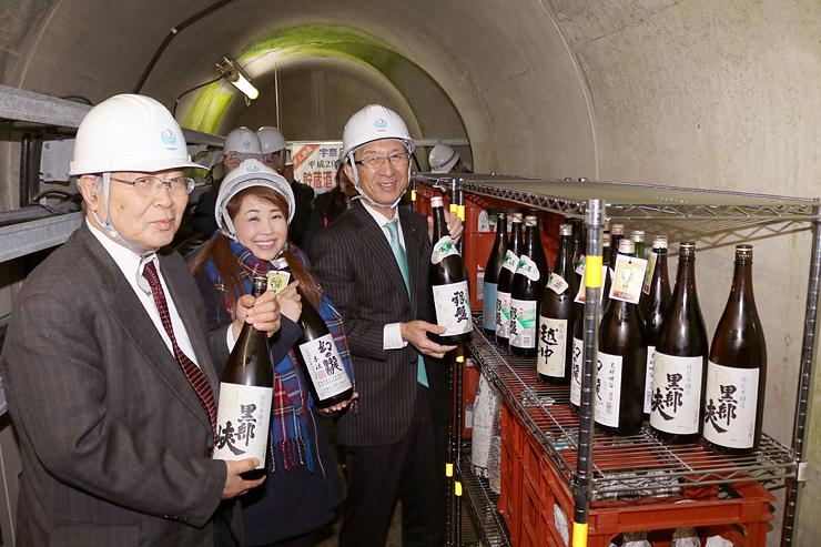 ダムの酒倉に地酒を蔵入れする河田会長(左)や堀内市長(右)ら=黒部市の宇奈月ダム