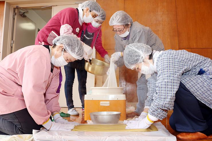 とち餅を平たく延ばす住民=富山市下タ南部公民館