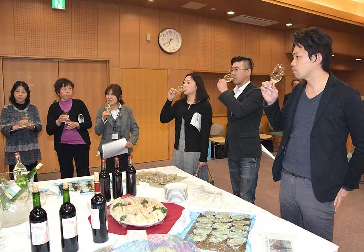 坂城町産のブドウで造った白ワインを試飲する人たち=16年2月