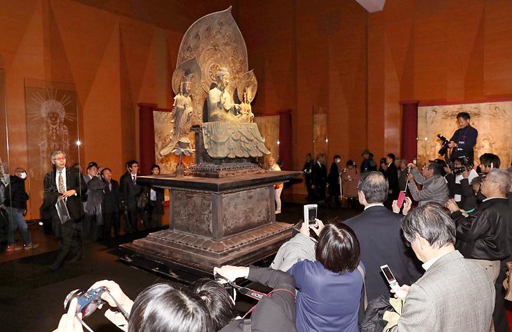 高岡銅器と井波彫刻の伝統技術に現代の先進技術を駆使して再現された釈迦三尊像に見入る来場者=ウイング・ウイング高岡