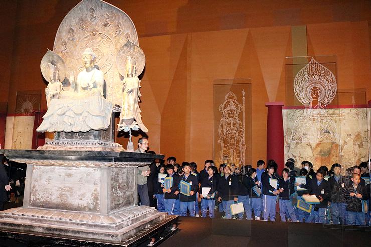 再現された法隆寺の釈迦三尊像を見学する児童ら