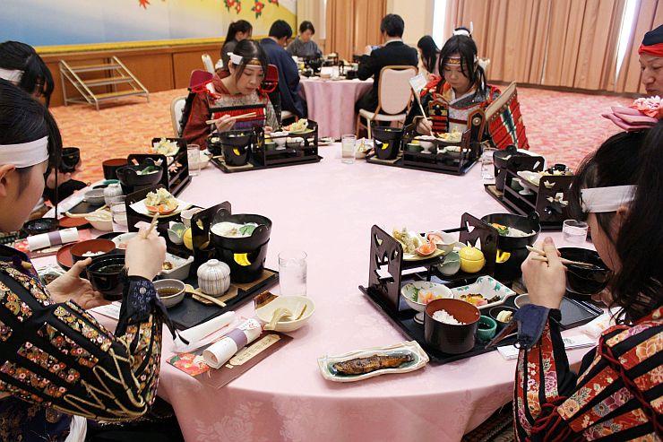 「板額御膳」を味わう板額会のメンバーら=12日、胎内市夏井のロイヤル胎内パークホテル