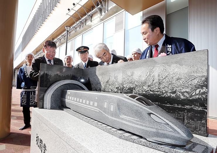 駅舎前に設置された北陸新幹線のモニュメント。関係者が設置を祝った=新高岡駅南口