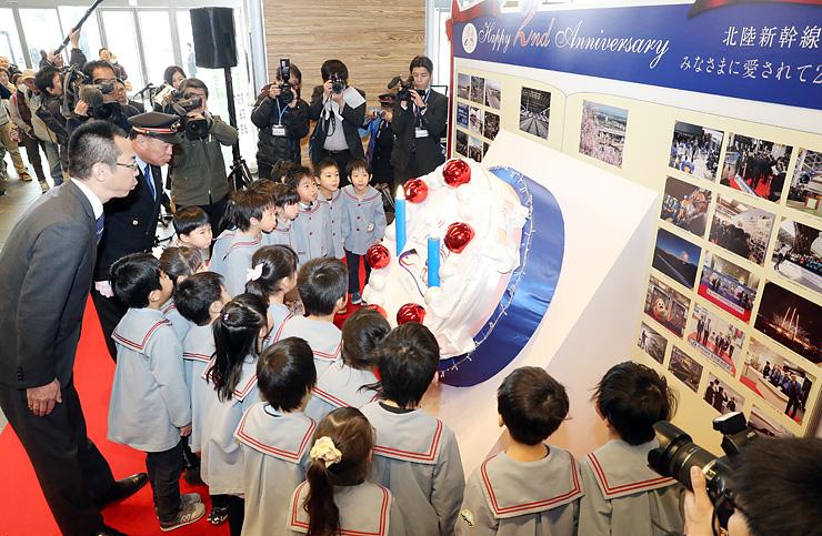 開業2周年を祝い、誕生ケーキオブジェのろうそくを吹き消す園児ら=JR富山駅コンコース新幹線改札前