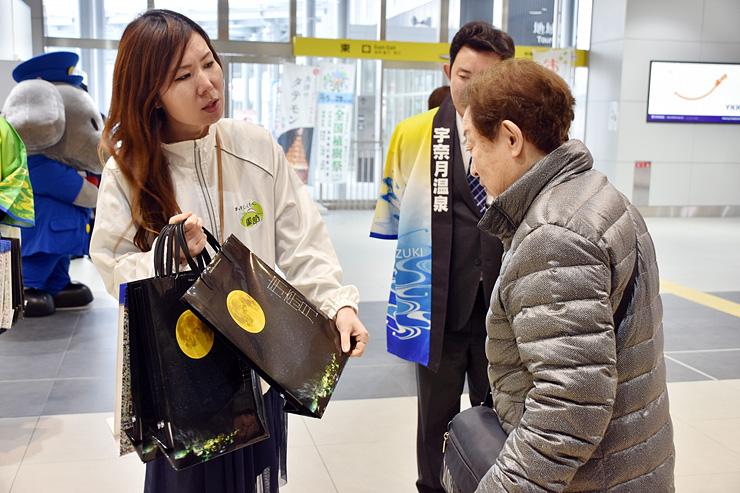 駅利用者にPRバッグを渡すN・P・Oのメンバー