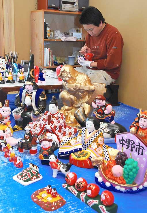 中野ひな市に向けて絵付けが進む中野人形。奈良さんが筆に心を込める