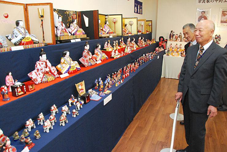 展示室に並べた中野土人形を眺める市川さん(右)