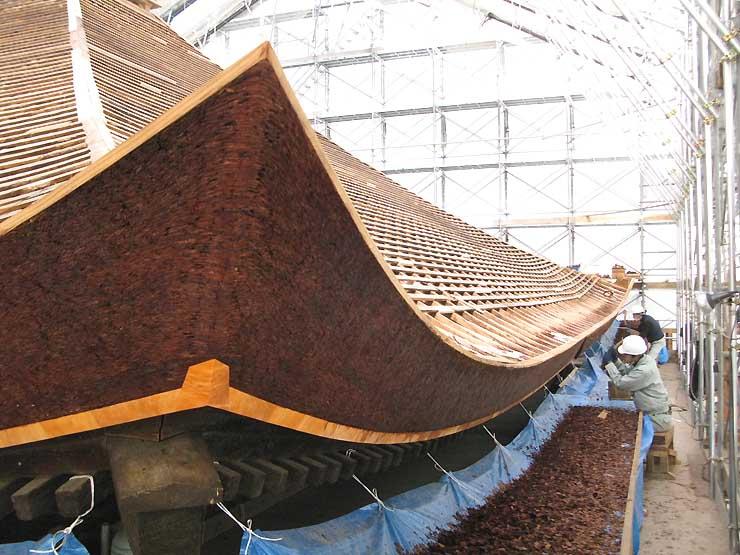 ヒノキの樹皮で整えられた経蔵の軒先。職人たちが手斧を手際良く使い、余分な皮を削り取った