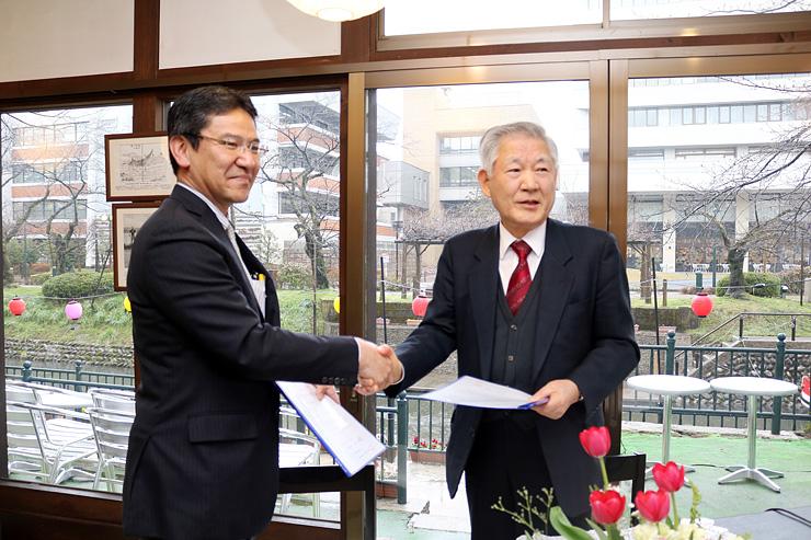 協定書を交わし、握手する金澤社長(左)と中村社長=松川茶屋