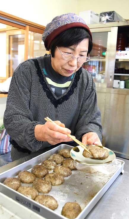 エゴマのおはぎを皿に載せる清水さん