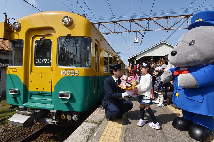 倉谷運転士(中央左)に花束を贈る蛇澤皐月ちゃん=電鉄黒部駅