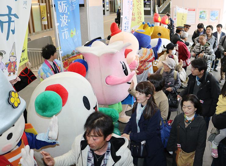 首都圏から団体専用臨時列車で到着し、歓迎を受ける観光客=新高岡駅