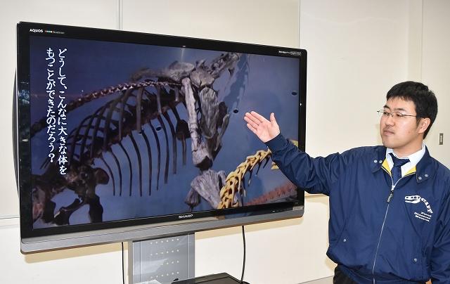 映像資料「竜脚類 巨大化の秘密」を解説する関谷研究員=29日、福井県勝山市の福井県立恐竜博物館