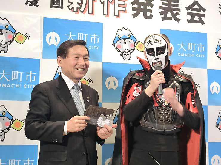 完成作品を発表する鉄拳さん(右)と牛越市長=東京・銀座
