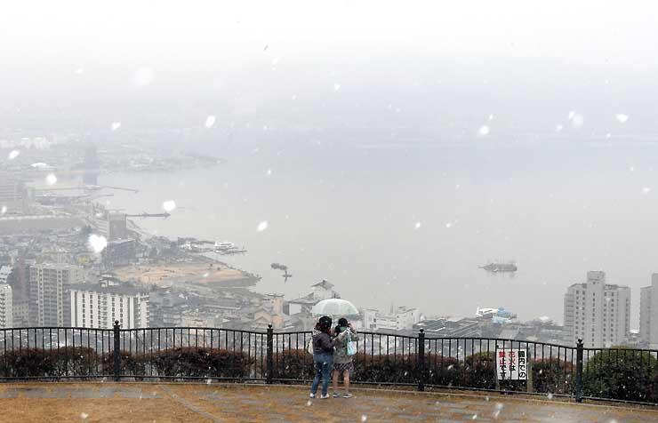 霧に包まれた諏訪湖と湖畔の街並み。時折、小雪も舞った=諏訪市の立石公園