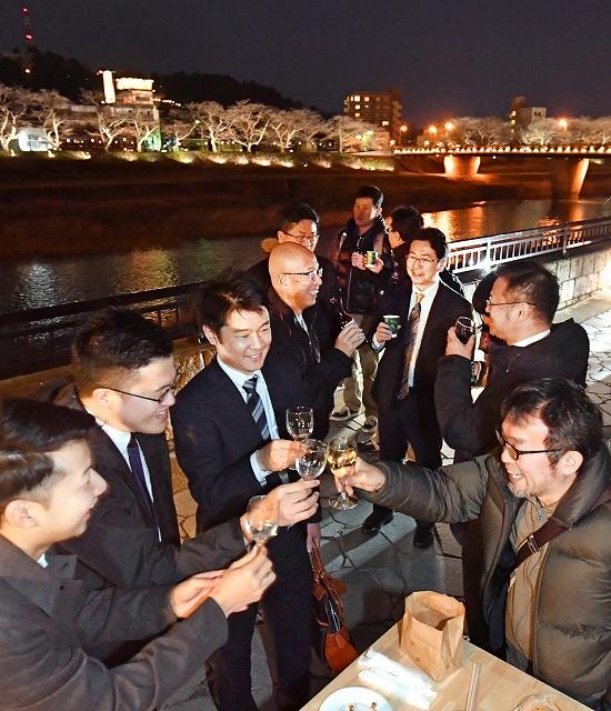 ライトアップされた桜並木をバックに、足羽川の川辺で乾杯する人たち=31日夜、福井市中央3丁目