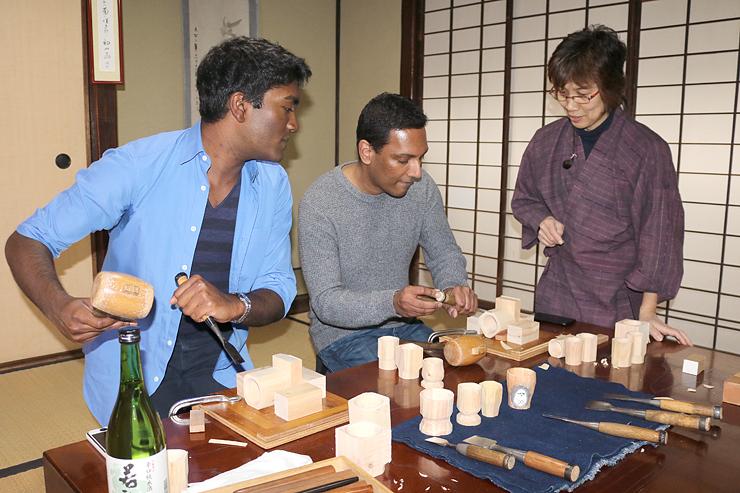 山根さん(右)の指導で、のみを手にぐい飲みの表面を削るランガンさん(中央)、ガナパシさん(左)=黒髪庵