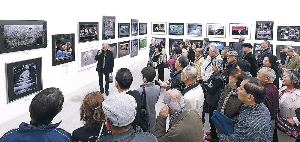 写真部門の解説に耳を傾ける愛好者=金沢21世紀美術館