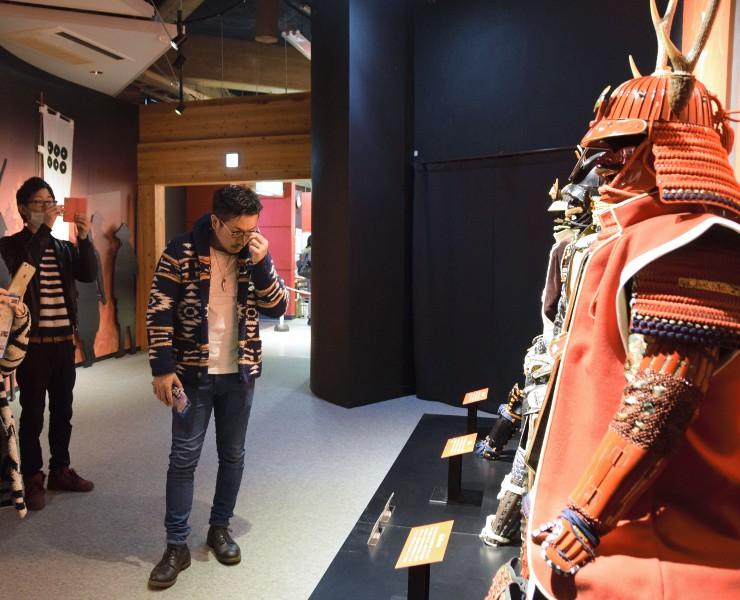 会場に展示された真田氏の甲冑のレプリカを写真に収める来場者