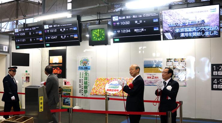新設した案内モニターを除幕し、システムの運用開始を祝う関係者=富山駅