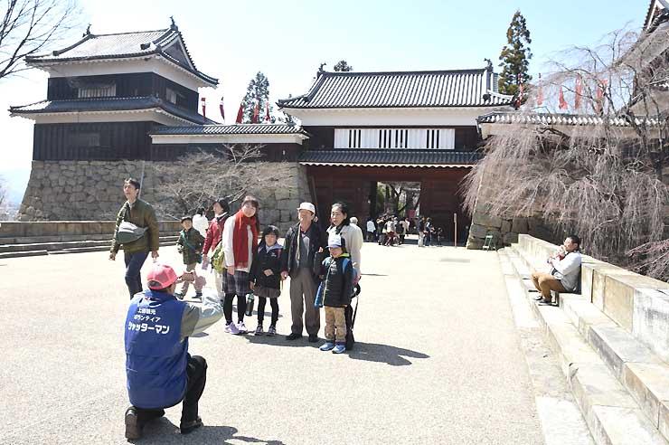 櫓門前で記念写真に納まる来場者。脇の桜が咲くのはもう少し先だ=2日