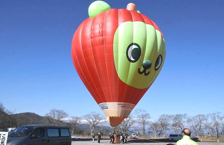 青空に浮かび上がる熱気球。奥の山並みは中央アルプス=3日、伊那市の高遠城址公園