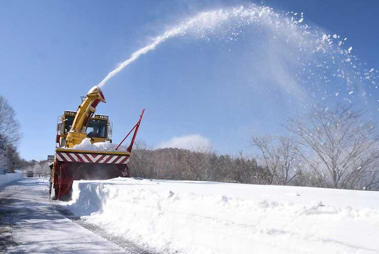 多い所で1メートルほど積もった雪を勢い良く飛ばす除雪車