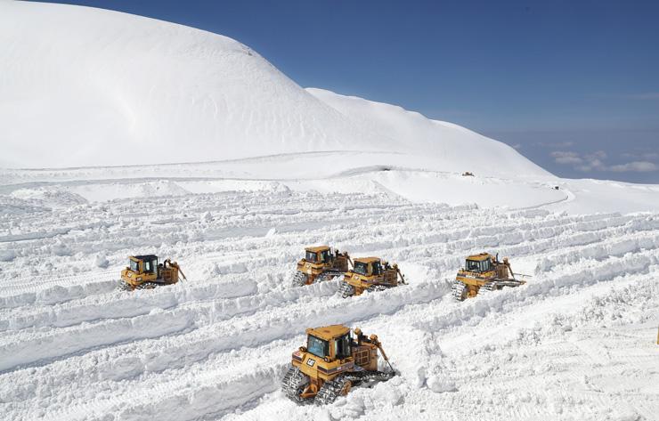 立山黒部アルペンルートの全線開通に向け、エンジン音を響かせながら除雪する重機=立山・室堂