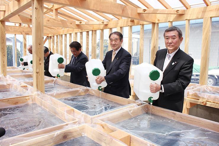 結晶箱に海洋深層水を注ぐ上田市長(右から2人目)ら出席者=滑川市坪川新