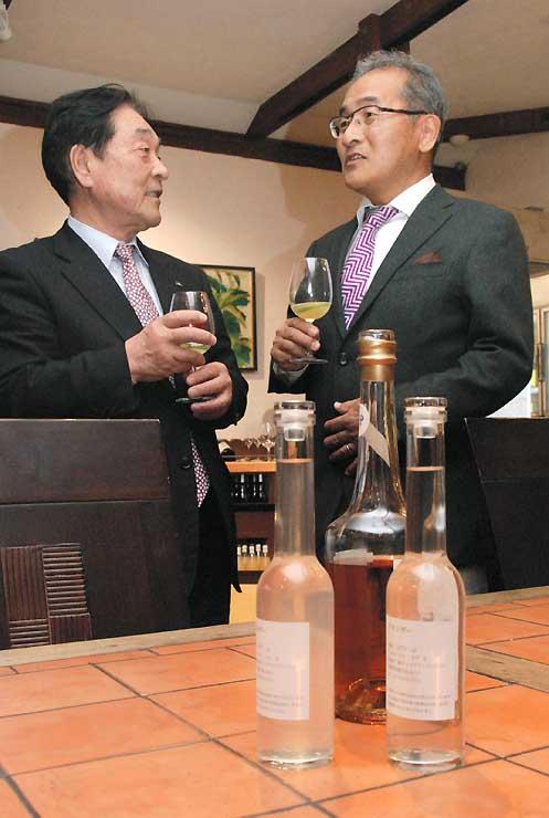 試験蒸留したリンゴのブランデーを前に話す久世社長(右)と峯村町長。熟成させると、手前奧の瓶のように深みのある色になる