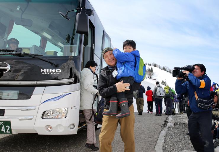 青空の下、立山高原バスを降り笑顔を見せる家族連れら=立山・弥陀ケ原