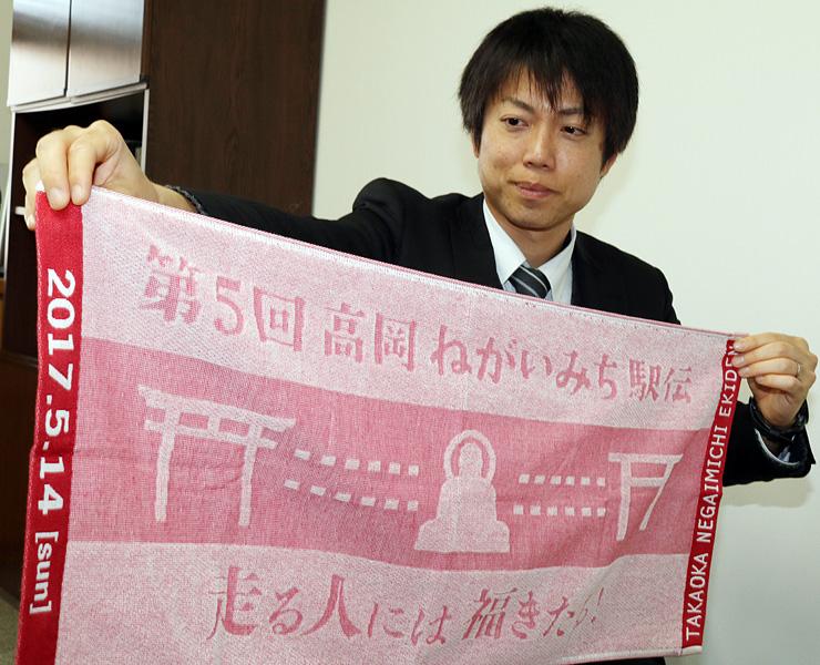 参加記念タオルを持ち、大会をPRする塚田さん=北日本新聞高岡支社