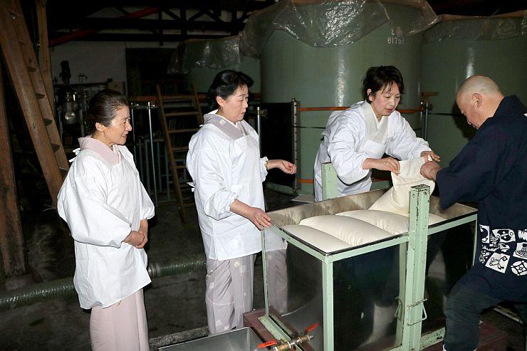 日本酒を搾る作業にチャレンジする女将たち=11日、新発田市の金升酒造