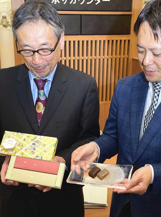 ようかんが入った箱を持つ栗田さん(左)。皿の左から、あずきと白あんのようかん
