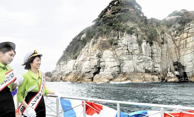 蘇洞門の大門、小門を案内するキララメイツの2人=15日、福井県の小浜湾